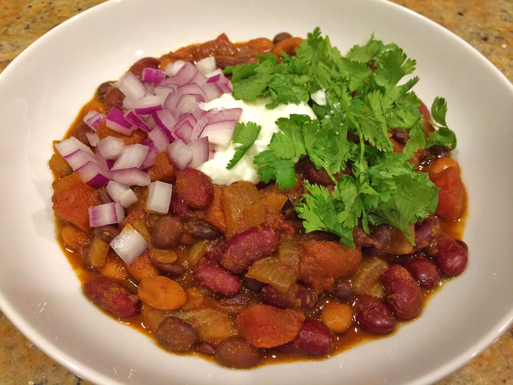 Meatless chili with 3 beans topped with cilantro, sour cream, and red onions.