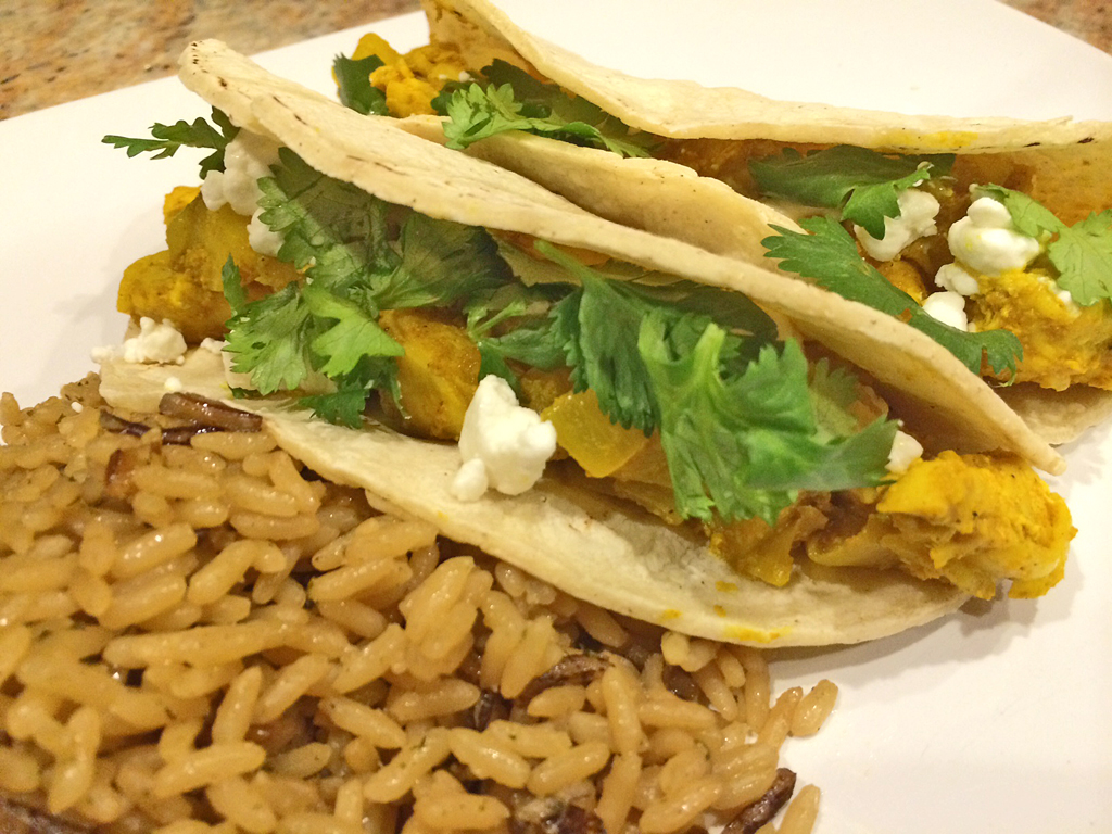 Chicken and pear tacos topped with goat cheese and cilantro with rice.