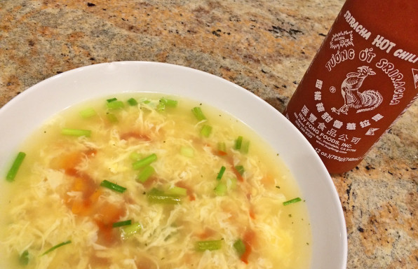 Egg Drop Sriracha Soup in white bowl with green onions and sriracha bottle.