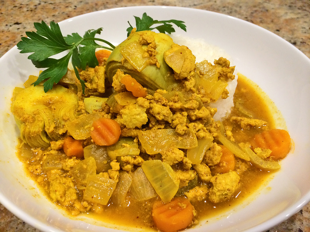 Chicken Moroccan stew with artichoke hearts atop white rice.