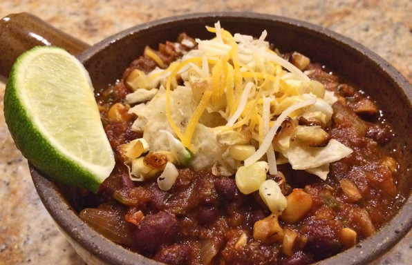 Meatless stew with black beans, salsa, cheese, corn, and a lime.